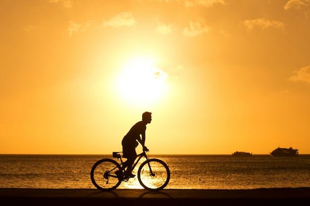 男は日没に対して屋外自転車に乗る。シルエット。
