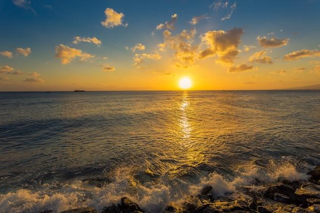 海の波は日没で岩を打つ