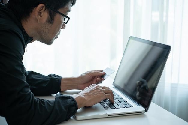 ラップトップコンピューターを介してオンラインショッピングし、クレジットカードで支払う男