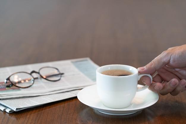 朝の熱いコーヒーカップを持っている男の手