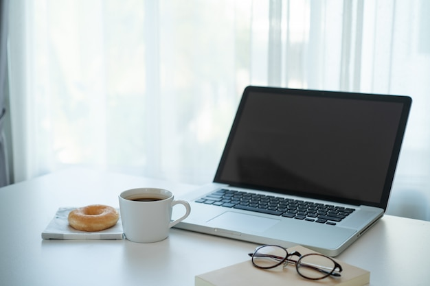 ノートパソコンとテーブルの上のホットコーヒーとドーナツ