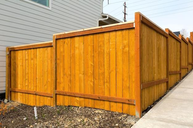 新しい家庭の裏庭の木製のフェンスの建設