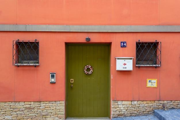 赤い壁の背景に閉じた緑の木製のドア