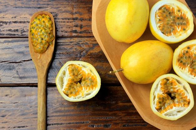 Желтые маракуйя и маракуйя отрезали пополам в деревянном шаре на деревянном столе.