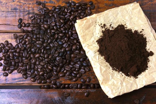 コーヒー豆の焙煎と素朴なテーブルの上の紙の上の挽いたコーヒー。上面図