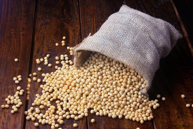 木製のテーブルの上の素朴な布の袋に生と新鮮な大豆