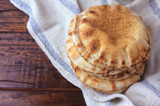 素朴な布の上の素朴な木製のテーブルで分離されたピタパン