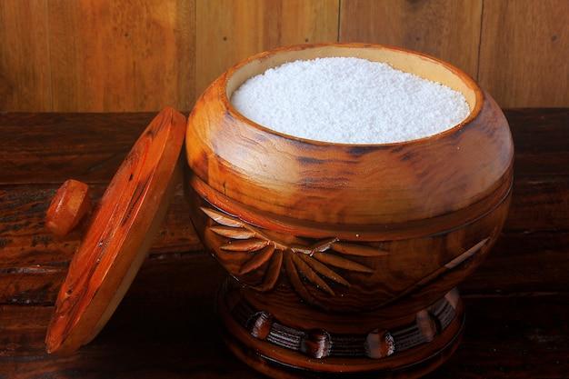 木製の背景に木製のボウルにタピオカ粉