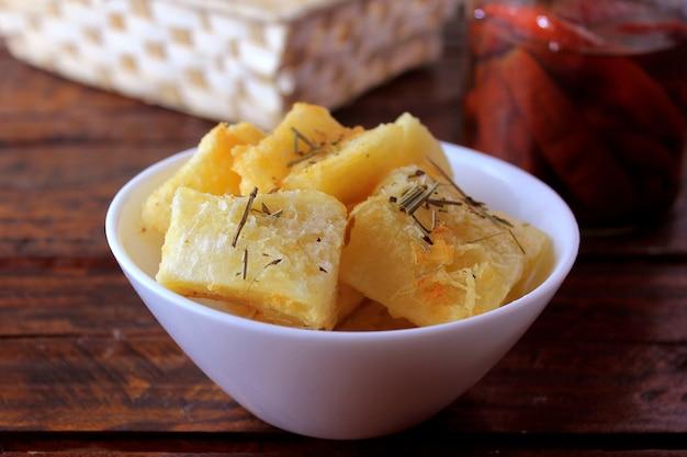 Вареная и жареная маниока (мандиока) в керамической миске на деревенский деревянный столик в ресторане