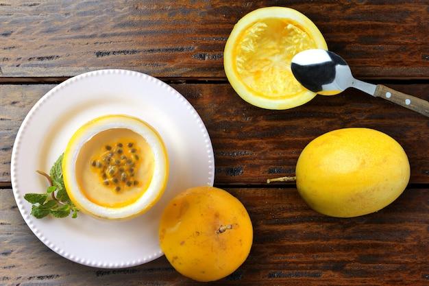 素朴な木製のテーブルを飾るプレート上のフルーツの皮でデザートパッションフルーツのムース