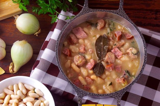 Суп из тушеного мяса или белой фасоли с колбасой, овощами, специями и травами подается в деревенской кастрюле на деревянном столе