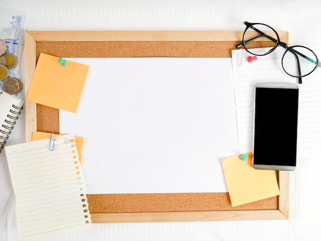 木の板、便箋、鉛筆、眼鏡、お金、携帯電話、カレンダーなどの周辺機器を備えた白紙の背景、
