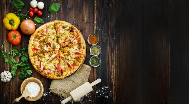 上面図、シーフードピザ、食材、野菜、トマト、チリ、マッシュルーム、ニンニクなどの周りに飾る野菜。木製のテーブルの背景に。
