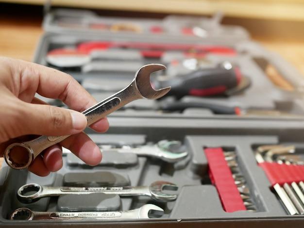 Рука человека держит гаечный ключ разных размеров в ящике для инструментов.