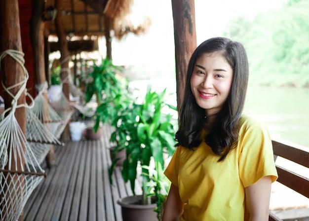 Симпатичная азиатская девушка, в желтой футболке, во время своего путешествия она улыбалась и позировала во многих моментах с зеленой природой.