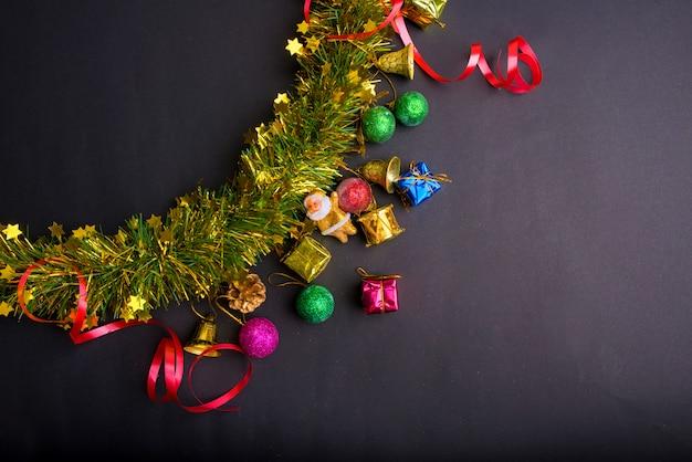 暗い黒背景のクリスマスの装飾。トップビュー、コピースペース。ボール、ギフトボックス、サンタクロース、リボン、松の枝、鐘。