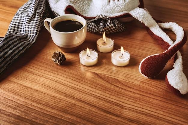 冬のコーヒーは、木製のテーブルにスカーフ、帽子、ろうそく、松の飾りです。暖かい色調。