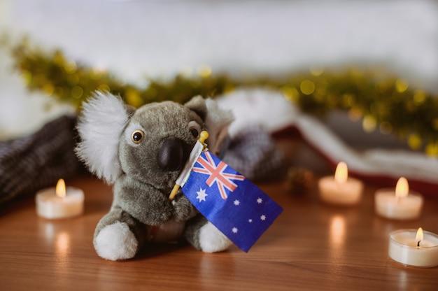 クリスマスの装飾の背景を持つオーストラリアの旗を持つコアラ。オーストラリアのために祈ってください。