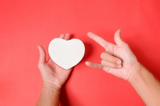 白いハート形のギフトボックスと赤の背景に愛のシンボルとして作られた手を保持している手。バレンタインギフトボックス。