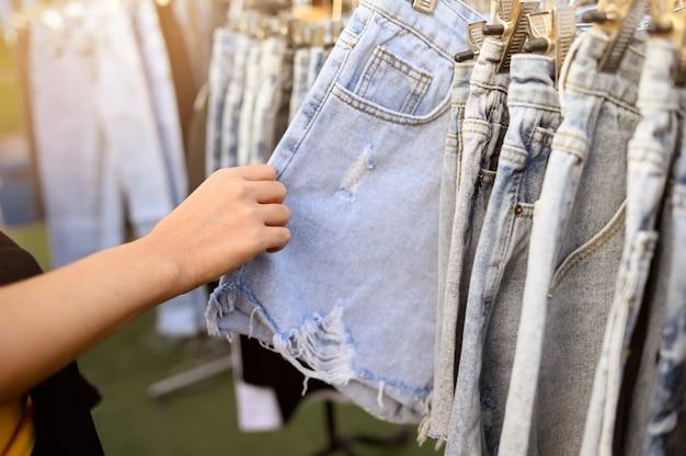 Человек, покупающий джинсы на барахолке