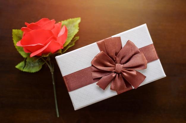 Вид сверху красной розы и белого подарка