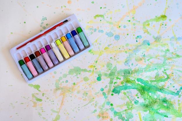 Цветная трубка в акварельной коробке на белой бумаге размазывает цвет, образование и художественный объект, вид сверху.