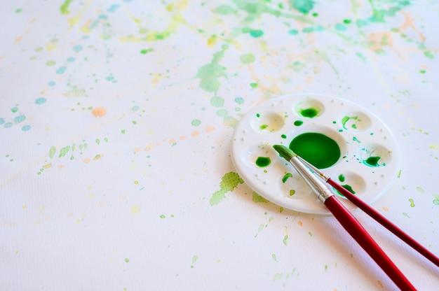 Кисти и акварельные краски, палитры на белой бумаге размазывают цветом, образование и арт-объект.