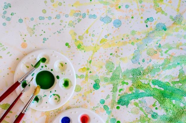 Кисти и акварельные краски, палитры на белой бумаге размазывают цветом, вид сверху.