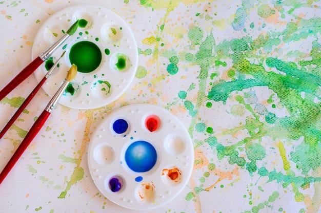 Кисти и акварельные краски, палитры на белой бумаге мажут цветом, образование и арт-объект, вид сверху.