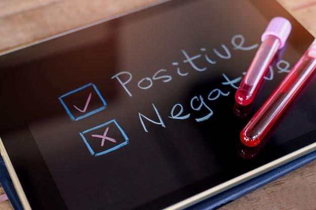 Трубка для забора крови на планшете с выбором отрицательного или положительного. коронавирусный анализ крови.