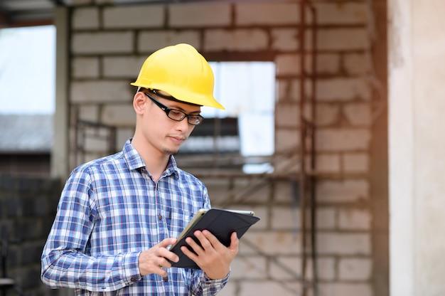 Инженеры используют таблетки для проверки конструкции. инженер в очках, глядя на планшет.