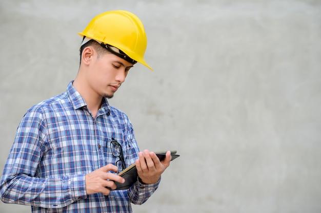 Инженеры используют планшеты для проверки конструкции. инженер с фоном - цемент.