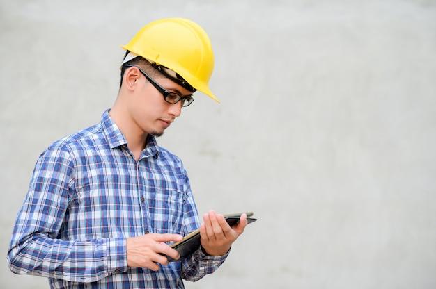 Инженер держа таблетку перед предпосылкой цемента. инженер проверка на строительство.
