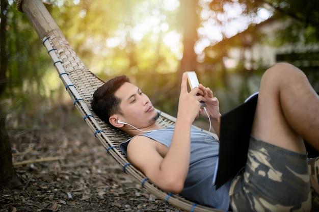 笑みを浮かべて、森の中の木製の担架で電話で遊ぶ男。家にいる。幸せな休日。
