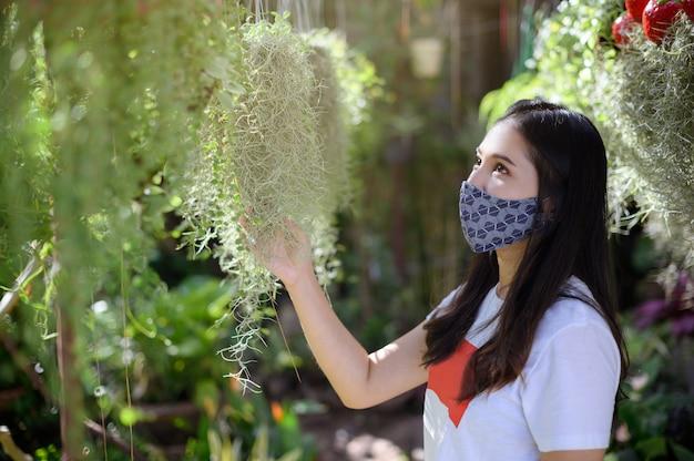 マスクを身に着けている女性は庭の木を買うことを選びます。