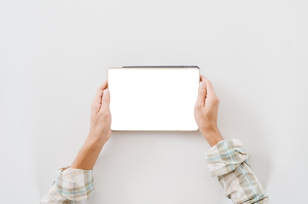 タブレットを保持しているクローズアップ手。白い背景で隔離された空の白いディスプレイデバイス。