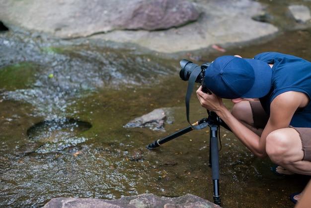 カメラを使用して森の滝の写真を撮る人