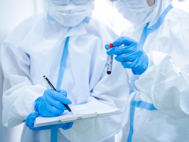 コロナウイルスのスクリーニングのために患者から血液サンプルを採取する前に、マスクを着用し、試験管を保持している女性医師。医療とヘルスケアの概念。