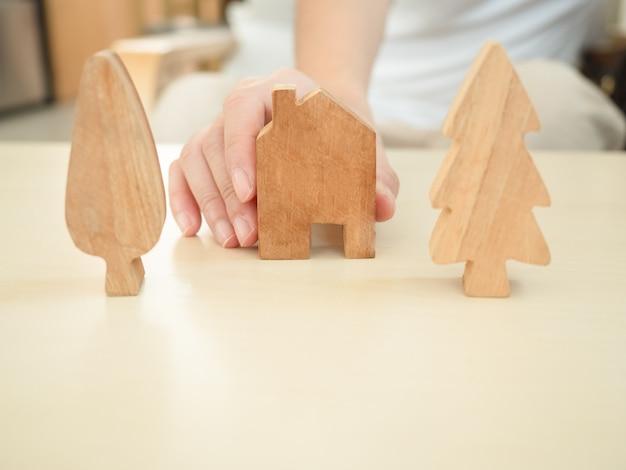 Женская рука держит дома и украшения деревьев из дерева, способствуя работе из дома и социальной дистанции, чтобы уменьшить распространение коронавирусной инфекции.