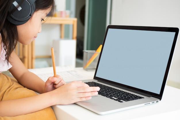 かわいいアジアの女の子は、家庭検疫中にオンラインレッスンを勉強するためにノートブックコンピューターを使用します。