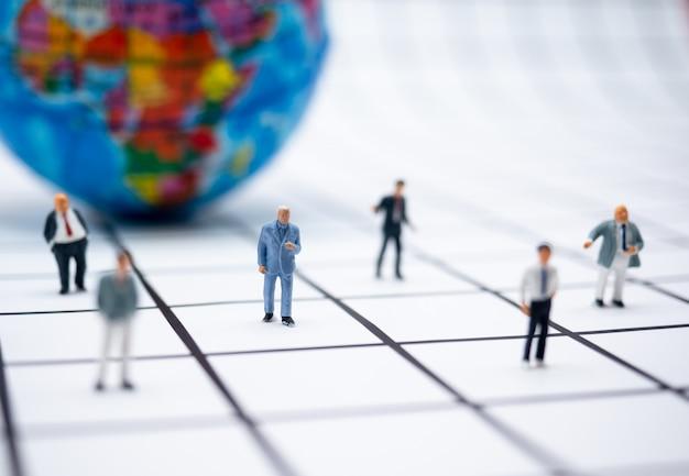 地球儀を持ったビジネスマンのミニチュアチームが、隔離中に自宅から、また社会的距離から作業します。