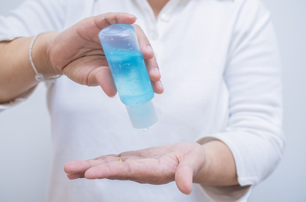 女性の手は、ポンプボトルからアルコールジェルを押して手をきれいにし、コロナウイルス感染を防ぎます。これは、流行病の最中の最初のセルフケアです。