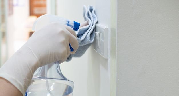 アルコールスプレーまたは防腐剤を使用してライトスイッチをきれいにする女性