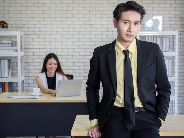 ラップトップを使用して文書を読んで、オフィスで働いているアジアのビジネスマンとビジネスウーマンは、新しい通常のライフスタイルである社会的距離を空けるためにデスクを用意しました