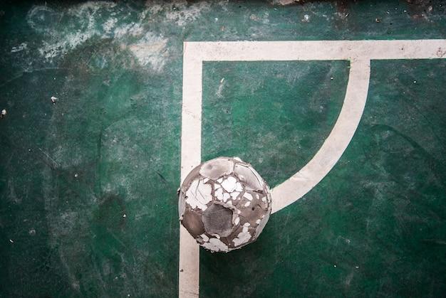 Старый футбольный мяч на сухом и потрескавшемся грунте