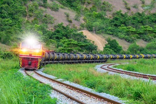 石油を輸送するタンカー車の鉄道は青々とした山々を走ります。