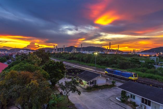夕焼けの空の背景を持つ工業用不動産工場。