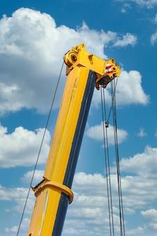 Мобильные строительные краны с жёлтыми телескопическими стрелами и большие башенные краны.