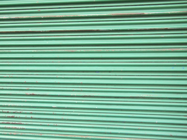 照らされたグランジ金属ローラーシャッタードア