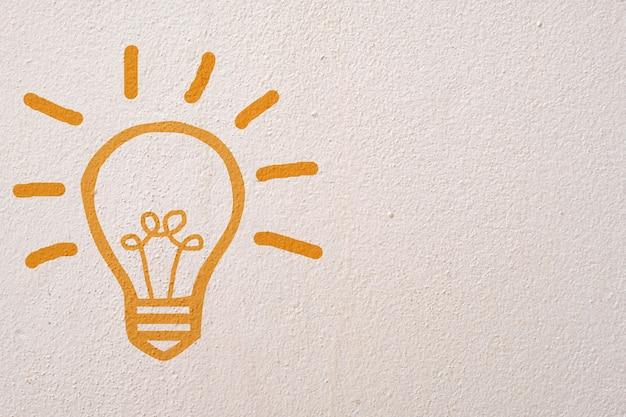 コンクリートの壁の背景に抽象的なオレンジ思考電球